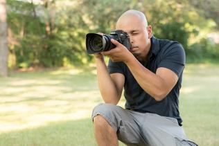 Christopher Bacchus knelt on a lawn in shorts and t-shirt using his professional camera
