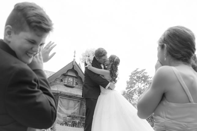 Kids reacting to bride and groom's kiss - Black and white photo by Christopher Bacchus