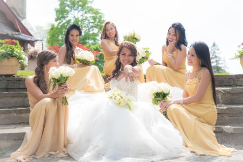 Bride with bridesmaids sitting on steps - Photo by Christopher Bacchus