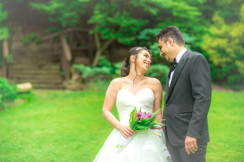 Bride and groom smiling at one another surrounded by greenery - Photo by Christopher Bacchus