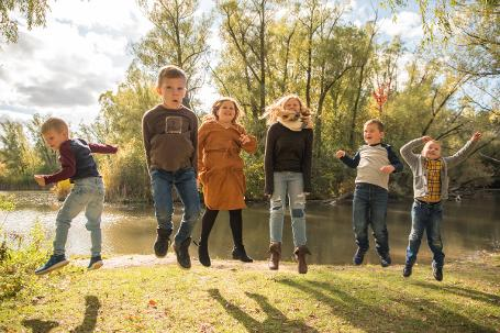 Kids jumping surrounded by autumn landscape - Photo by Christopher Bacchus