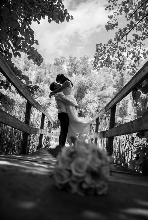 Bride being held off of the ground by her groom, standing on a bridge in the distance with bouquet resting in the foreground - Black and white photo by Christopher Bacchus