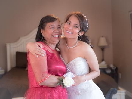 Bride and mother embraced and smiling - Photo by Christopher Bacchus